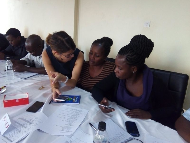 A project manager shows a group of community health workers how to use their mobile data collection app